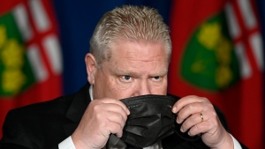 Ontario Premier Doug Ford puts his mask on after speaking at a press conference at Queen's Park, in Toronto, Friday, April 16, 2021. (THE CANADIAN PRESS/Frank Gunn)
