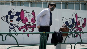 A man wearing a protective mask stands near drawings of Miraitowa and Someity, official mascots for the Tokyo 2020 Olympics and Paralympics, on a construction wall in Tokyo, on April 20, 2021. (Eugene Hoshiko / AP)