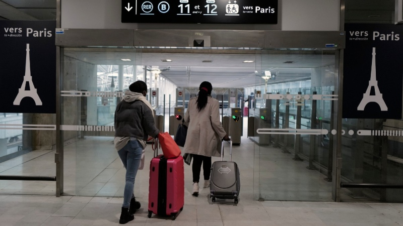 Passengers arrive to take the suburb train at Paris Charles de Gaulle Airport in Roissy, north of Paris, on Feb. 1, 2021. (Francois Mori / AP)