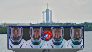 Members of the SpaceX Crew 2, from left, Thomas Pesquet, of the European Space Agency, NASA astronauts Megan McArthur, Shane Kimbrough, and Akihiko Hoshide, of the Japan Aerospace Exploration Agency, are shown on a video screen as the SpaceX Falcon 9 with the crew Dragon capsule sits on Launch Complex 39A, on April 21, 2021. (Chris O'Meara / AP)