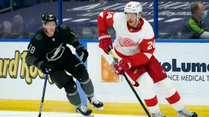 Detroit Red Wings defenseman Jon Merrill (24) carries the puch around Tampa Bay Lightning left wing Ondrej Palat (18) during the second period of an NHL hockey game Saturday, April 3, 2021, in Tampa, Fla. (AP Photo/Chris O'Meara)