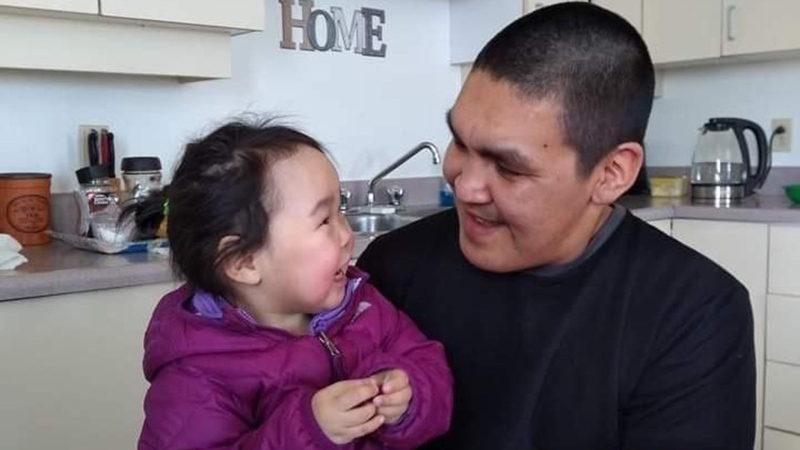Abraham Natanine, who was shot and killed by police in May 2020 at the age of 31, sits with his daughter in Clyde River, Nunavut in this undated handout image. (THE CANADIAN PRESS / HO-Michelle Illauq)