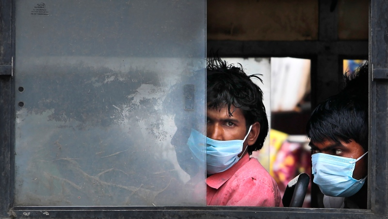 Migrant laborers sit in a bus to travel to their villages following a six-day lockdown put into place to control the rising cases of coronavirus infections, in New Delhi, India, Tuesday, April 20, 2021. (AP Photo/Manish Swarup)