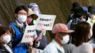 "Organizers hold signs to spectators that read: ""Avoid crowding! Wear masks"" during the Tokyo Olympic torch relay in Tobe, Ehime prefecture, southwestern Japan, Thursday, April 22, 2021. (Kyodo News via AP)"