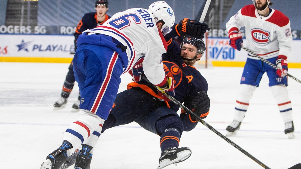 Edmonton Oilers' Leon Draisaitl (29) is checked by Montreal Canadiens' Shea Weber (6) during second period NHL action in Edmonton on Wednesday, April 21, 2021.THE CANADIAN PRESS/Jason Franson