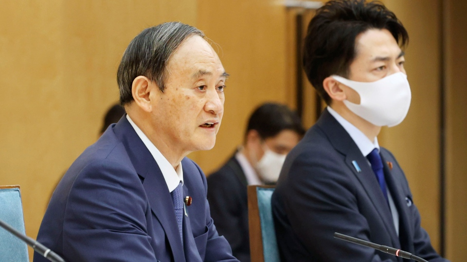 Japanese Prime Minister Yoshihide Suga, left, and Minister of the Environment Shinjiro Koizumi attend the global warming meeting at the prime minister's office in Tokyo, Thursday, April 22, 2021. (Kyodo News via AP)
