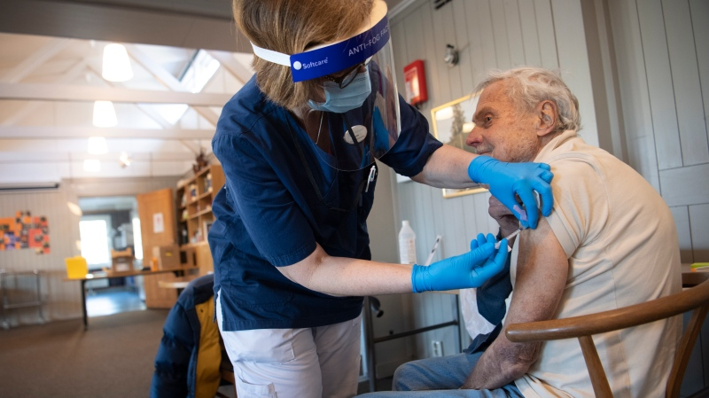 A health worker administers a Pfizer's COVID-19 vaccine to a man at a temporary vaccination clinic in a church in Sollentuna, north of Stockholm, Sweden, Tuesday March 2, 2021. (Fredrik Sandberg/TT via AP)