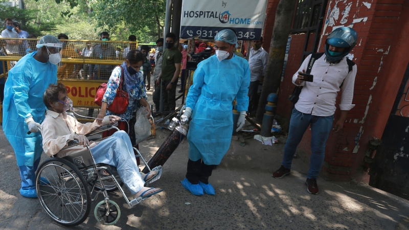 Health works assist a patient as he is brought to a COVID-19 care center in New Delhi, India, Thursday, April 22, 2021. The world's fastest pace of spreading infections and the highest daily increase in coronavirus cases are pushing India further into a deepening and deadly health care crisis. (AP Photo)