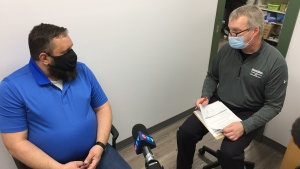 Pharmacist Scott Coulter, right, explains to client Bob Ironside what side effects to expect after receiving the AstraZeneca COVID-19 vaccine in London, Ont. on Thursday, April 22, 2021. (Bryan Bicknell / CTV News)