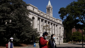 In this March 11, 2020, file photo, people wear masks while walking past Wheeler Hall on the University of California campus in Berkeley, Calif. (AP Photo/Jeff Chiu, File)