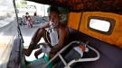 A COVID-19 patient wearing oxygen mask waits inside an auto rickshaw to be attended and admitted in a dedicated COVID-19 government hospital in Ahmedabad, India, Thursday, April 22, 2021. (AP Photo/Ajit Solanki)