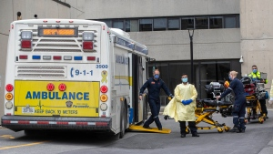 Paramedics walk back gurneys to the multi-patient transport at Kingston General Hospital after dropping off COVID-19 patients from the GTA area, in Kingston, Ont., on Thursday Apr. 22, 2021. (THE CANADIAN PRESS/Lars Hagberg)