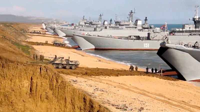 This handout photo taken from a video released on Friday, April 23, 2021 by Russian Defense Ministry Press Service shows, Russian troops board landing vessels after drills in Crimea. Russian Defense Minister Sergei Shoigu on Thursday ordered troops back to their permanent bases after a massive military buildup that caused Ukrainian and Western concerns. (Russian Defense Ministry Press Service via AP)