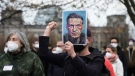 A man holds a poster with a drawing of Russian opposition leader Alexei Navalny, as he protests against the jailing of the Russian opposition leader near the chancellery in Berlin, Germany, on April 21, 2021. (Markus Schreiber / AP)