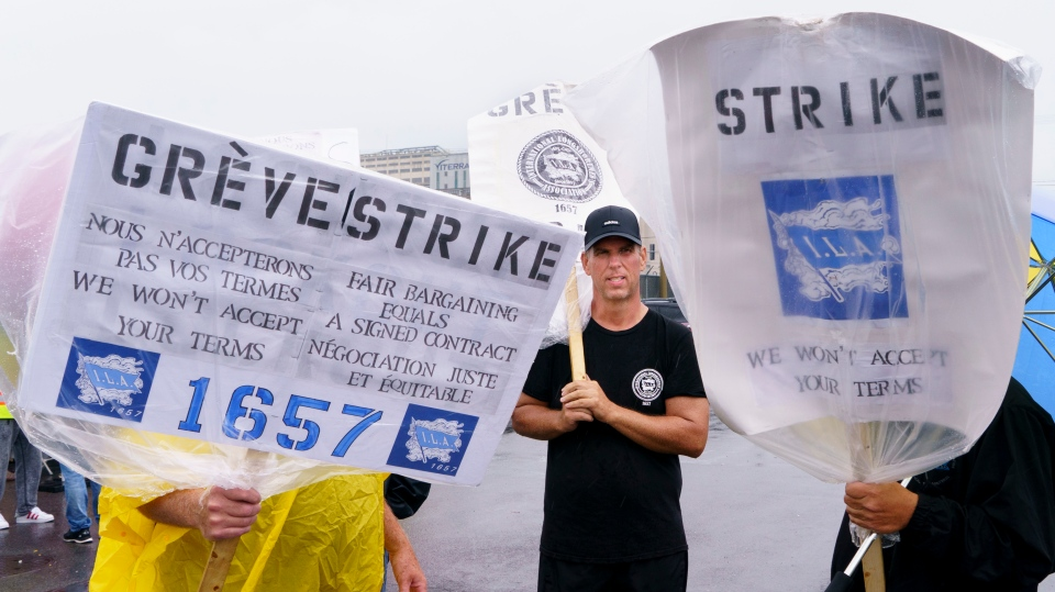 Striking Port of Montreal workers brave the elements to walk the picket line in Montreal on Monday, August 17, 2020. The workers have been without a contract for over two years. Without a change of heart, the longshormen will go on strike again on Monday. THE CANADIAN PRESS/Paul Chiasson
