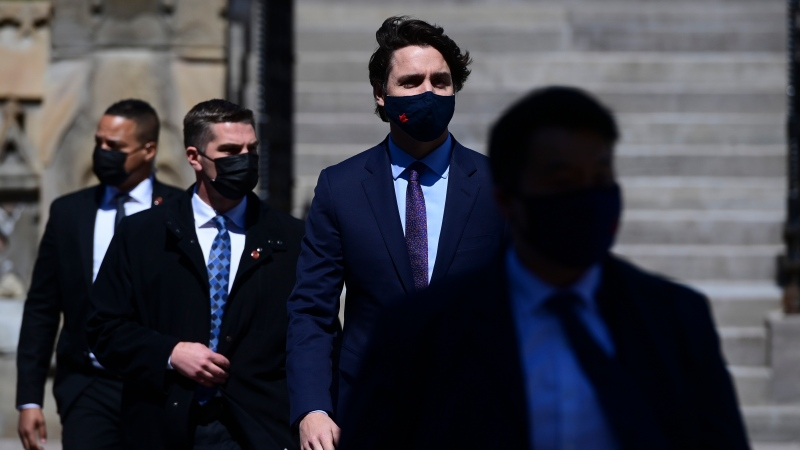 Prime Minister Justin Trudeau, centre, makes his way to hold a press conference in Ottawa on Friday, April 23, 2021, during the COVID-19 pandemic. THE CANADIAN PRESS/Sean Kilpatrick