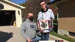 Jakob and Jason Smith are seen outside their woodshop where they create Canadian flags out of old wood pallets and wood and composite hockey sticks. (Sean Irvine CTV News)