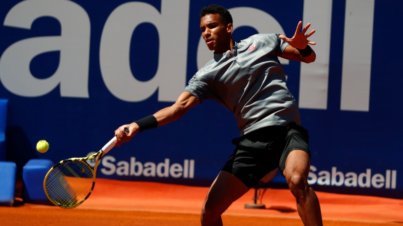 Felix Auger-Aliassime of Canada returns the ball to Stefanos Tsitsipas of Greece during a quarterfinal Godo tennis tournament in Barcelona, Spain, Friday, April 23, 2021. (AP Photo/Joan Monfort)