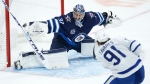 Toronto Maple Leafs' John Tavares (91) scores on Winnipeg Jets goaltender Connor Hellebuyck (37) during second period NHL action in Winnipeg on Saturday, April 24, 2021. (THE CANADIAN PRESS/John Woods)