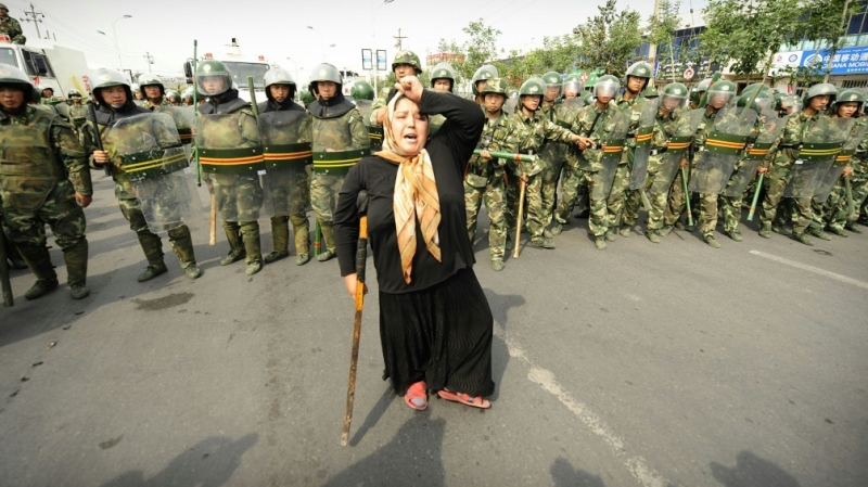 This file photo taken on July 7, 2009 shows Chinese riot police watching a Muslim ethnic Uyghur woman protesting in Urumqi, the capital of China's Xinjiang region. (AFP)