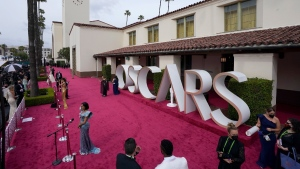 Regina King, foreground, is interviewed on the red carpet at the Oscars at Union Station in Los Angeles, on April 25, 2021. (Mark Terrill / AP)