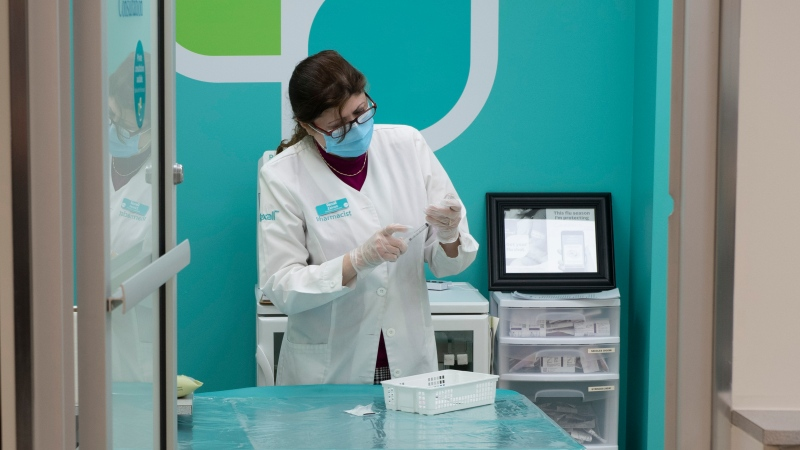 Pharmacist Zaineb Hassan prepares COVID-19 vaccines to administer at a pharmacy in Ottawa on Friday, April 23, 2021. (Adrian Wyld/THE CANADIAN PRESS)