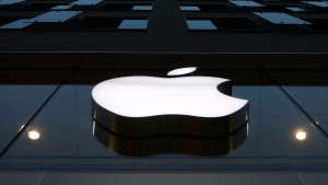 In this Wednesday, Dec. 16, 2020, file photo, the logo of Apple is illuminated at a store in the city center in Munich. (AP Photo/Matthias Schrader, File)