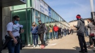 People line up outside an immunization clinic to get their Oxford-AstraZeneca COVID-19 vaccine in Edmonton, Tuesday, April 20, 2021. THE CANADIAN PRESS/Jason Franson