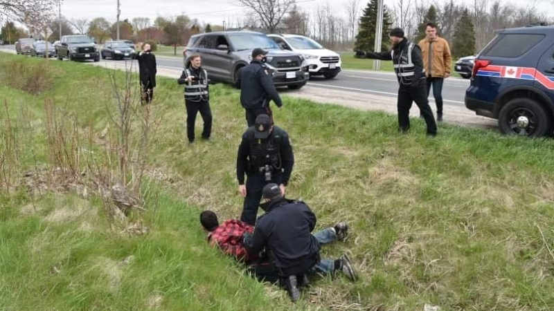 Police are seen arresting a man across the highway from the Church of God Restoration in Aylmer, Ont. on Sunday, April 26, 2021. (Source: Brett Hueston / Aylmer Express)