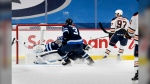 Edmonton Oilers' Connor McDavid (97) scores on Winnipeg Jets goaltender Connor Hellebuyck (37) during second period NHL action in Winnipeg, Monday, April 26, 2021. THE CANADIAN PRESS/Fred Greenslade