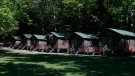 In this file photo from June 4, 2020 photo, a row of cabins can be seen at Camp Winnebago summer camp in Fayette, Maine. (AP Photo/Robert F. Bukaty)