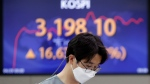 A currency trader walks near the screen showing the Korea Composite Stock Price Index (KOSPI) at the foreign exchange dealing room in Seoul, South Korea, Thursday, April 29, 2021. (AP Photo/Lee Jin-man)