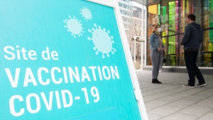People are shown outside a COVID-19 vaccination site in Montreal, Sunday, April 25, 2021, as the COVID-19 pandemic continues in Canada and around the world. THE CANADIAN PRESS/Graham Hughes