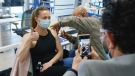 An employee's vaccination is recorded by a coworker at a COVID-19 vaccination clinic at CAE headquarters in Montreal, on Monday, April 26, 2021. A provincial program to provide vaccinations at large businesses began today at the Montreal headquarters of the flight simulation technology manufacturer. THE CANADIAN PRESS/Paul Chiasson