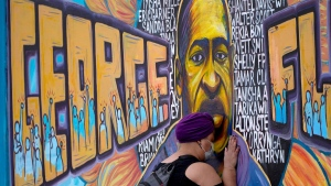 Damarra Atkins paid her respects to George Floyd at a mural at George Floyd Square in Minneapolis, on April 23, 2021. (Julio Cortez / AP)