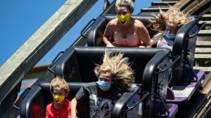 People wear face masks while riding the wooden roller coaster at Playland amusement park at the Pacific National Exhibition, in Vancouver, on Sunday, August 9, 2020. (Darryl Dyck / THE CANADIAN PRESS)