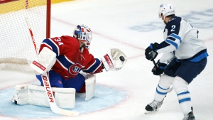 Montreal Canadiens goaltender Jake Allen gloves a shot from Winnipeg Jets' Dylan DeMelo during second period NHL hockey action in Montreal on Friday, April 30, 2021. THE CANADIAN PRESS/Paul Chiasson
