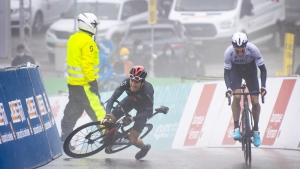 Geraint Thomas from Great Britain of team Ineos Grenadiers, left, falls, next to the winner of the stage Michael Woods from Canada of team Israel Start-Up Nation, right, during the 4th stage, a 161,3 km race between Sion and Thyon 2000 at the 74th Tour de Romandie UCI ProTour cycling race in Thyon-Les Collons, Switzerland, Saturday, May 1, 2021. (KEYSTONE/Jean-Christophe Bott, via AP)