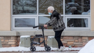 A woman walks outside the Roberta Place Long Term Care home in Barrie, Ont. on Monday, January 18, 2021. The home has seen an outbreak of COVID-19 among staff and residents. THE CANADIAN PRESS/Frank Gunn