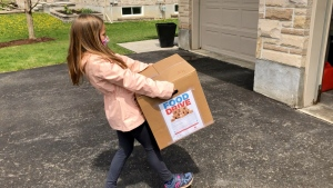 Jayda Arnott carrying one of 15 boxes of food she collected for her birthday food drive. (Dave Charbonneau / CTV News Ottawa)