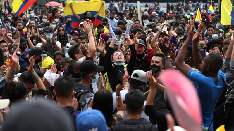 People shout slogans during a demonstration against government-proposed tax reform, marking May Day, or International Workers' Day, gathered in Bolivar Square in Bogota, Colombia, Saturday, May 1, 2021, amid the new coronavirus pandemic. (AP Photo/Fernando Vergara)
