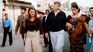 In this Dec. 5, 2005, file photo, Bill Gates, founder and chairman of Microsoft Corp., centre, and his wife Melinda, left, walk on a street in Dhaka, Bangladesh. (AP Photo/Gazi Sarwar, File)