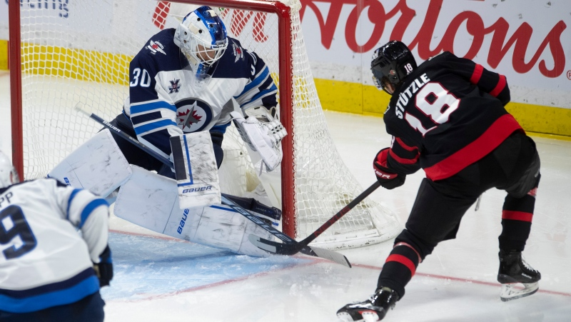 Winnipeg Jets goaltender Laurent Brossoit makes a pad save on Ottawa Senators left wing Tim Stutzle during third period NHL action in Ottawa, Monday, May 3, 2021. THE CANADIAN PRESS/Adrian Wyld
