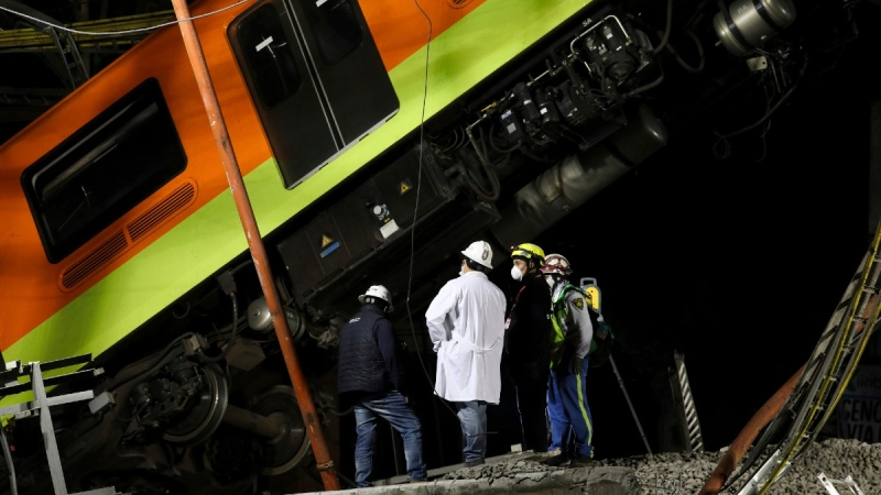 Workers at the scene where Mexico City subway cars fell when a section of Line 12 collapsed, on May 4, 2021. (Marco Ugarte /AP)