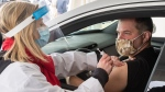 Alex Smirnov gets a COVID-19 vaccination from Annie Halinka Sanson at a demonstration of a drive-through vaccination site, Tuesday, May 4, 2021 in Montreal. The site will be able to give 4,000 doses a day.THE CANADIAN PRESS/Ryan Remiorz