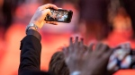 Actor Tony Curran holds up a fans cell phone as he poses for a selfie on the red carpet during the Toronto International Film Festival on Thursday September 6, 2018. THE CANADIAN PRESS/Chris Young