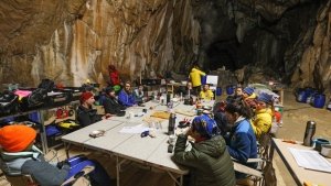 "In this photo provided by the Human Adaptation Institute on Saturday, April 24, 2021, members of the team taking part in the ""Deep Time"" study gather in the Lombrives Cave in Ussat les Bains, France. After 40 days in voluntary isolation, 15 people participating in a scientific experiment have emerged from a vast cave in southwestern France. Eight men and seven women lived in the dark, damp depths of the Lombrives cave in the Pyrenees to help researchers understand how people adapt to drastic changes in living conditions and environments. They had no clocks, no sunlight and no contact with the world above. (Human Adaptation Institute via AP)"