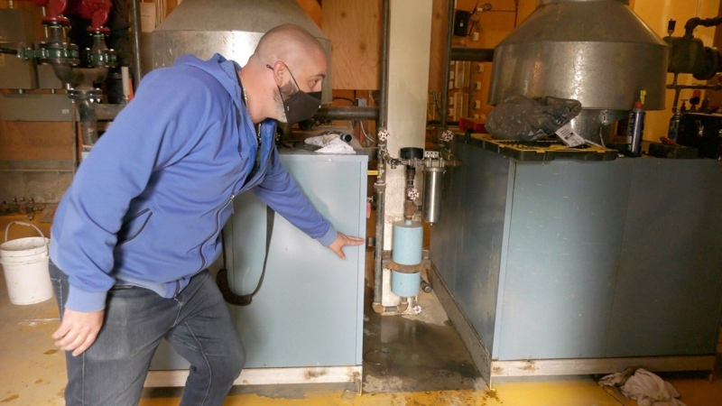 Property Manager Russell Bly shows how high the water came in the utility room