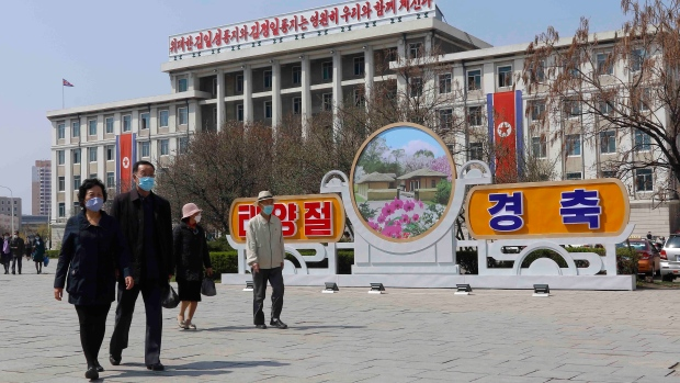 People walk in a street near the Arch of Triumph on the Day of the Sun, the birth anniversary of late leader Kim Il Sung, in Pyongyang, North Korea Thursday, April 15, 2021. (AP Photo/Cha Song Ho)