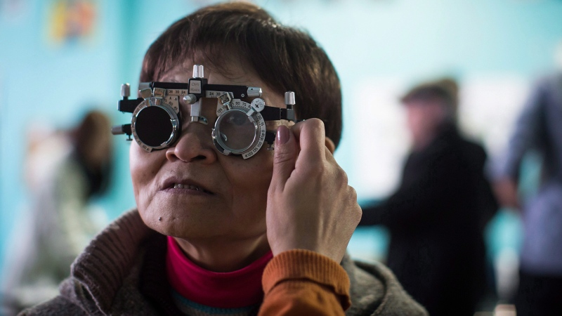 Bao Qin Song is fitted with a prescription by Dr. Alicia Ramirez at a makeshift eye clinic in the Downtown Eastside of Vancouver, on Sunday, March 4, 2018. THE CANADIAN PRESS/Darryl Dyck